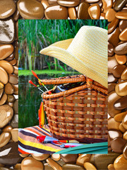 Cowboy hat, wicker basket,  spool andfishing tackle in the natur