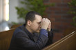 Handsome young man praying in a church