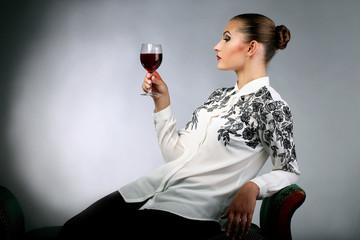 Молодая девушка на диване с бокалом вина