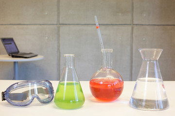 Glassware,goggles on desk in laboratory,laptop in background