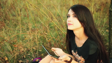 Young happy woman with tablet computer on meadow