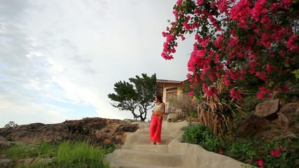 young woman walking down the stairs from house on mountains .