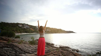 Young woman standing on a rock beach and rises hands. Flying