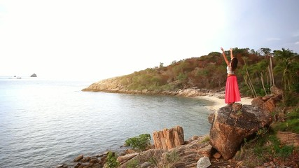 Young woman standing on a rock beach and rises hands. Koh Samui