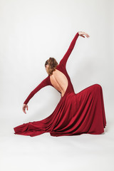 Girl in red dress dancing in the studio