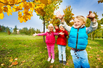 Group of kids playing with yellow leaves in park