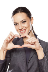 Beautiful smiling woman making a heart shape with her fingers