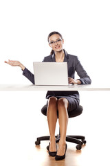 Smiling business woman sitting at a table with a laptop
