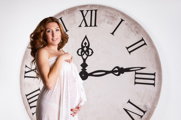 Young beautiful pregnant woman on a white background with giant