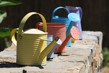Color watering can on wall