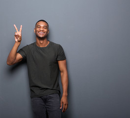 Young man smiling showing hand peace sign
