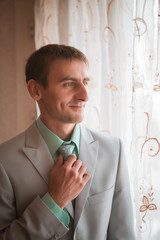 Portrait of young groom tying tie