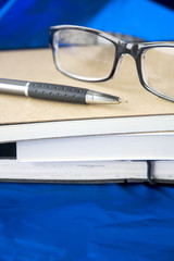glasses and pen on books