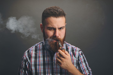 Bearded man smoking wooden pipe