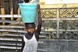 Afrikanisches Mädchen trägt Wassereimer