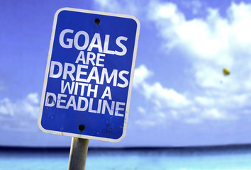 Goals Are Dreams With a Deadline sign with a beach