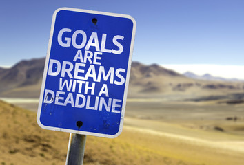 Goals Are Dreams With a Deadline sign with a desert