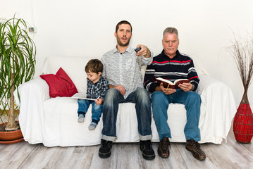 Son, father and grandfather sitting together on a white sofa