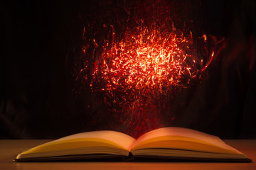 Open book with magic lights on dark background