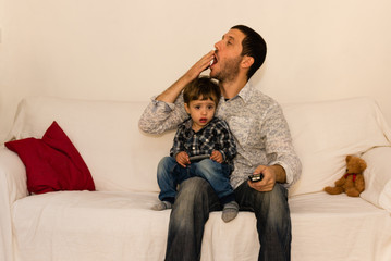 Father and son watching tv on a white sofa