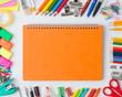 Leinwandbild Motiv Blank orange notebook with colourful crayons