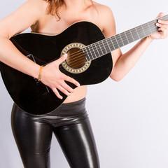Femme torse nu, guitare et pantalon moulant