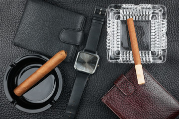 Two ashtray with cigars, two purses and watches on the natural l