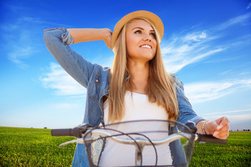 Young stylish woman with a bicycle in a field