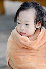 Wet Asian baby girl in brown towe.