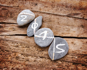 2015 written on a lign of stones on a wooden background