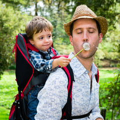 Baby with father travelling and blowing a dandelion