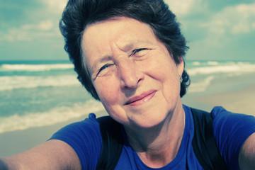 Selfie portait of happy senior woman on the beach