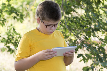 The boy in glasses looks tablet computer at nature