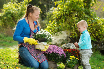 Young woman with a child are planted flowers in the gardenм