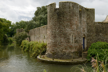 wall and round tower on moat at Bishop palace ,Wells