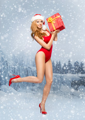 Young and sexy Santa girl in the red swimsuit with a Christmas p