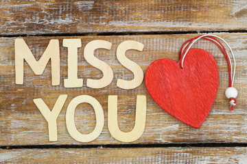 """Miss you"" written with wooden letters next to red wooden heart"