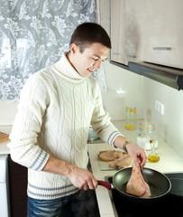 man cooking  steak  at home kitchen