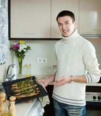 man with cooked fish on  frying pan