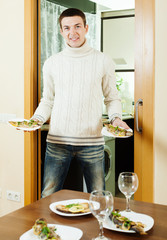 guy serving festive table with  fish