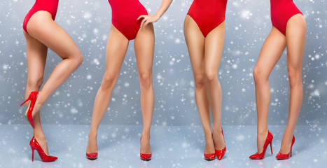 Beautiful legs of young and sporty women in red swimsuits
