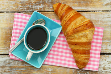 Butter croissant and black coffee on pink checkered cloth