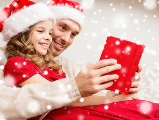 smiling father and girl in santa hats reading book