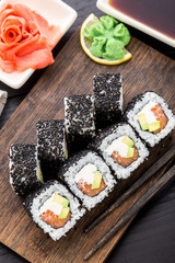 Salmon sushi roll covered with sesame