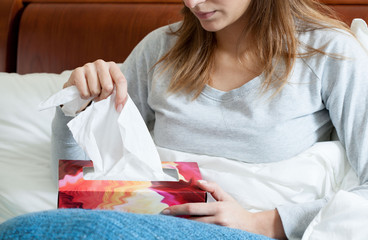 Sick woman with box of tissues