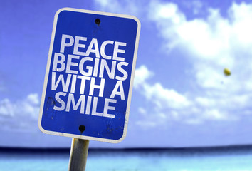 Peace Begins With a Smile sign with a beach on background