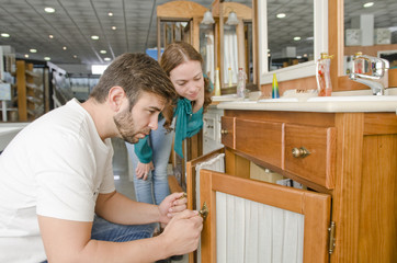 Couple looking sink in furniture shop