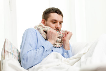 ill man wearing scarf lying in bed at home
