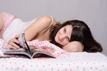 girl thumbs through a magazine while lying in bed