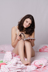 Girl sitting on bed and reading a magazine